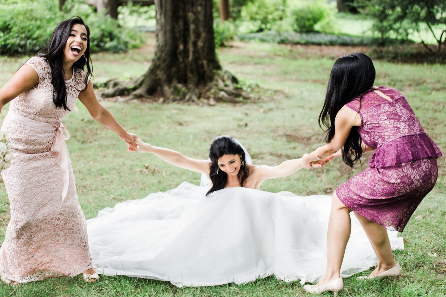 Bridesmaids help bride get up from the ground in a candid photo