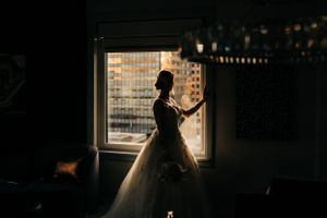 bride-looking-out-window-savory-hotel-desmoines-iowa-raelyn-ramey-photography