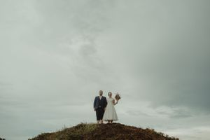 couple-standing-on-hill-cedar-rapids-ashton-hill-barn-raelyn-ramey-photography