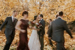 wedding party-running-around-couple-kissing-omaha-nebraska-raelyn-ramey-photography