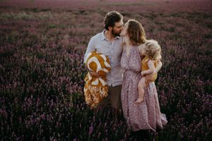 family-standing-in-flower-field-kissing-winterset-iowa-raelyn-ramey-photography