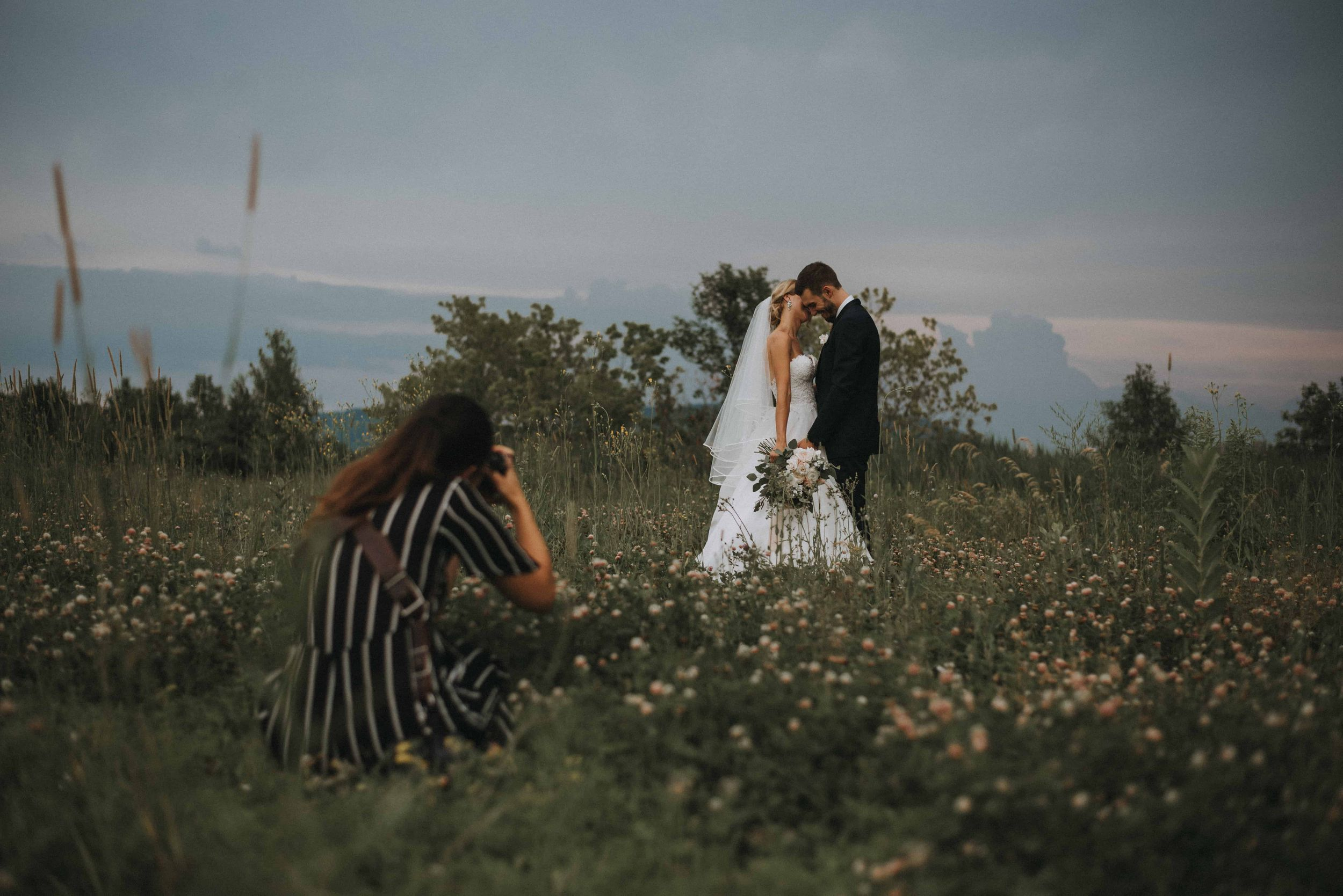 Raphaëlle Granger laying down in a flower field to get the perfect angle for this wedding session