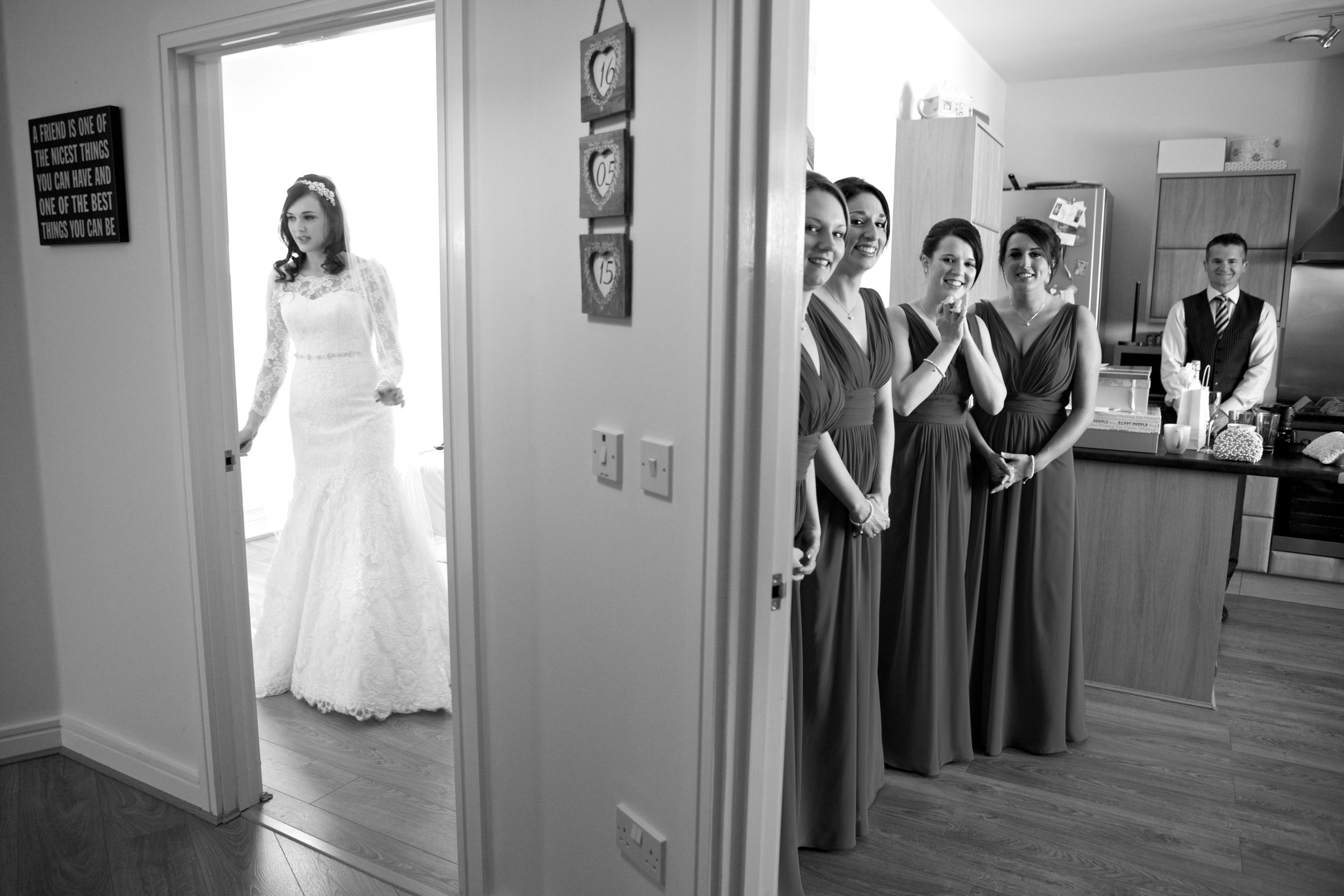 bride takes a last look in the mirror before the wedding ceremony while the bridesmaids wait to see her in her dress