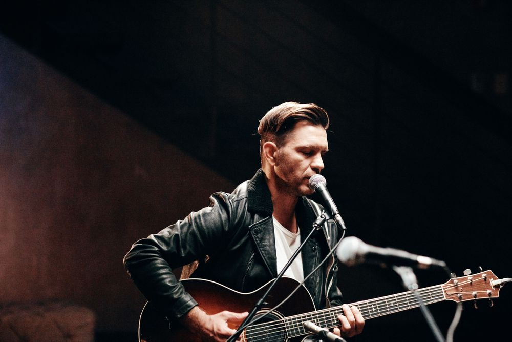 Andy Grammer strumming his distressed sunburst acoustic guitar at Only In Nashville. Photo: Joel Alexander.