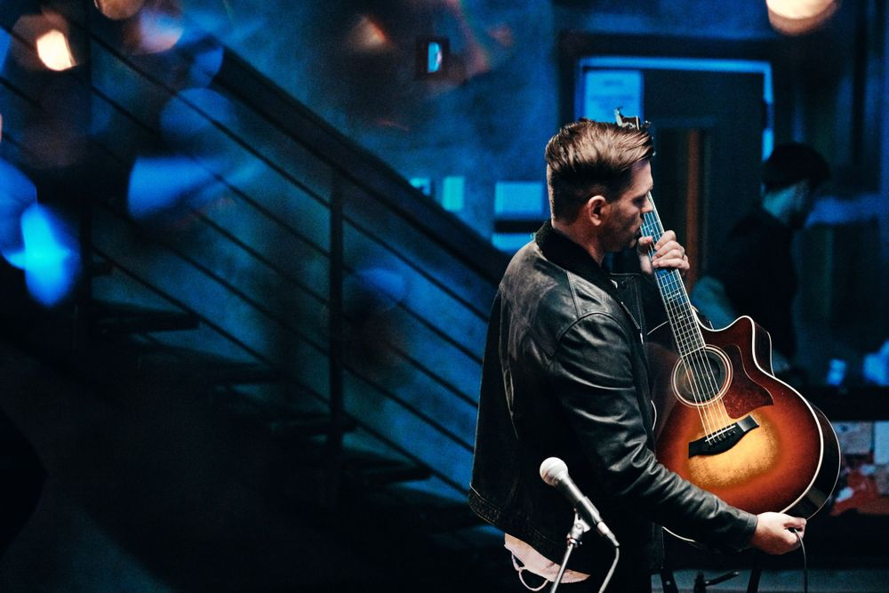 Andy Grammer unplugging his distressed sunburst acoustic guitar at Only In Nashville. Photo by Joel Alexander.