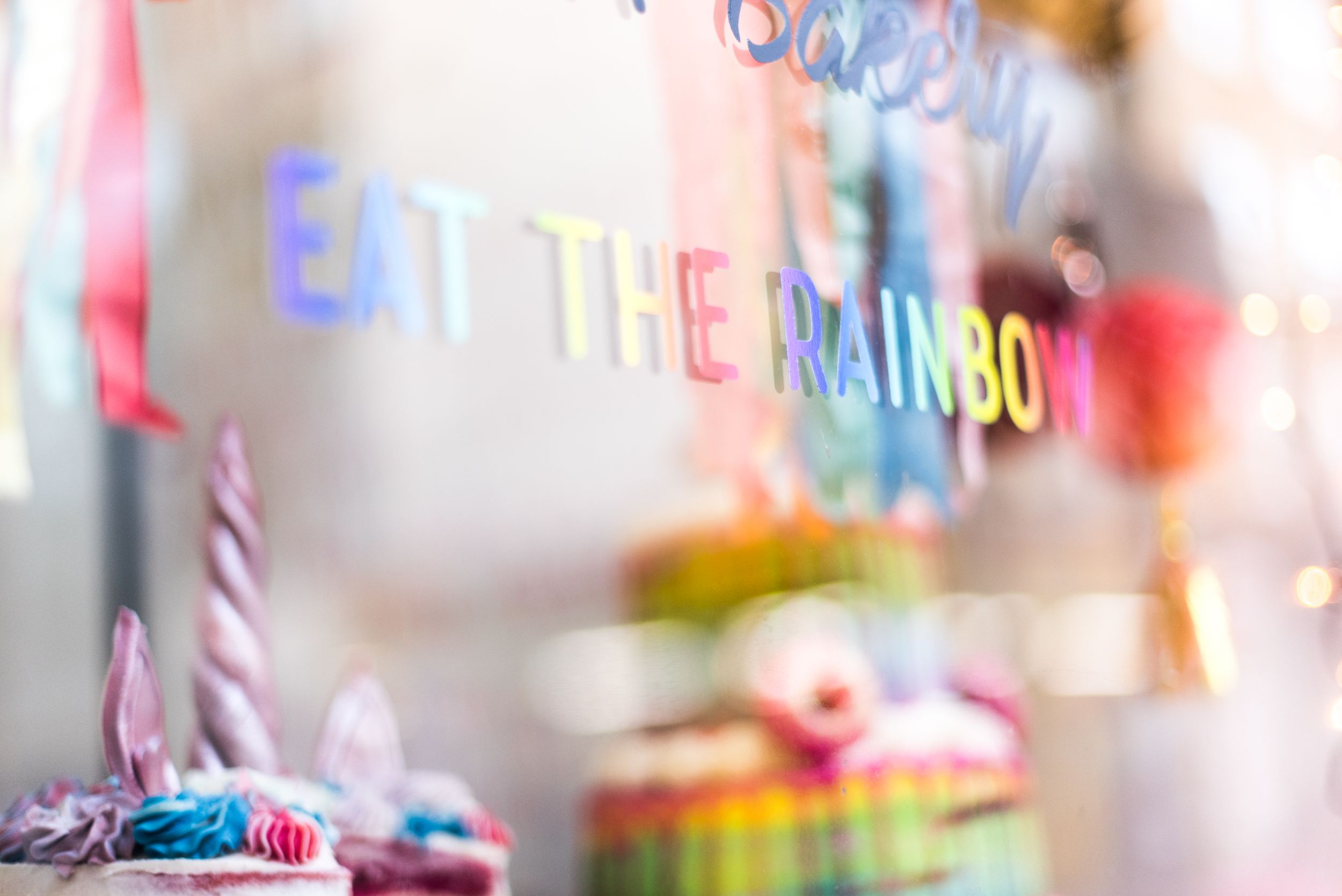 Colorful bakery window with rainbow reference