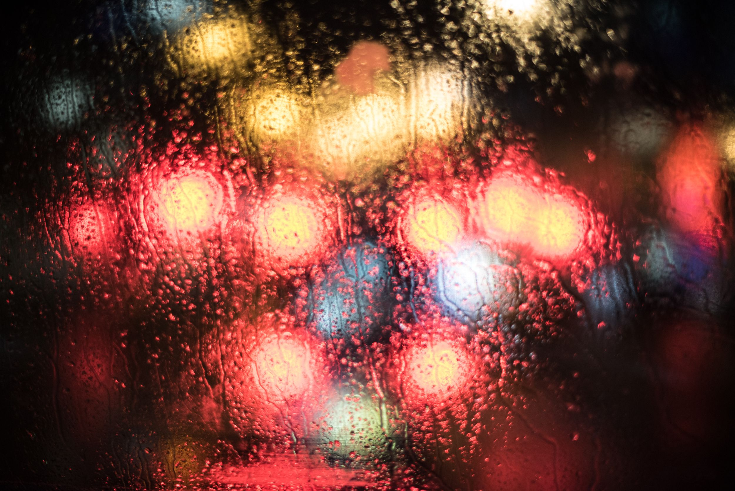 Colorful lights through a windshield on a rainy London evening
