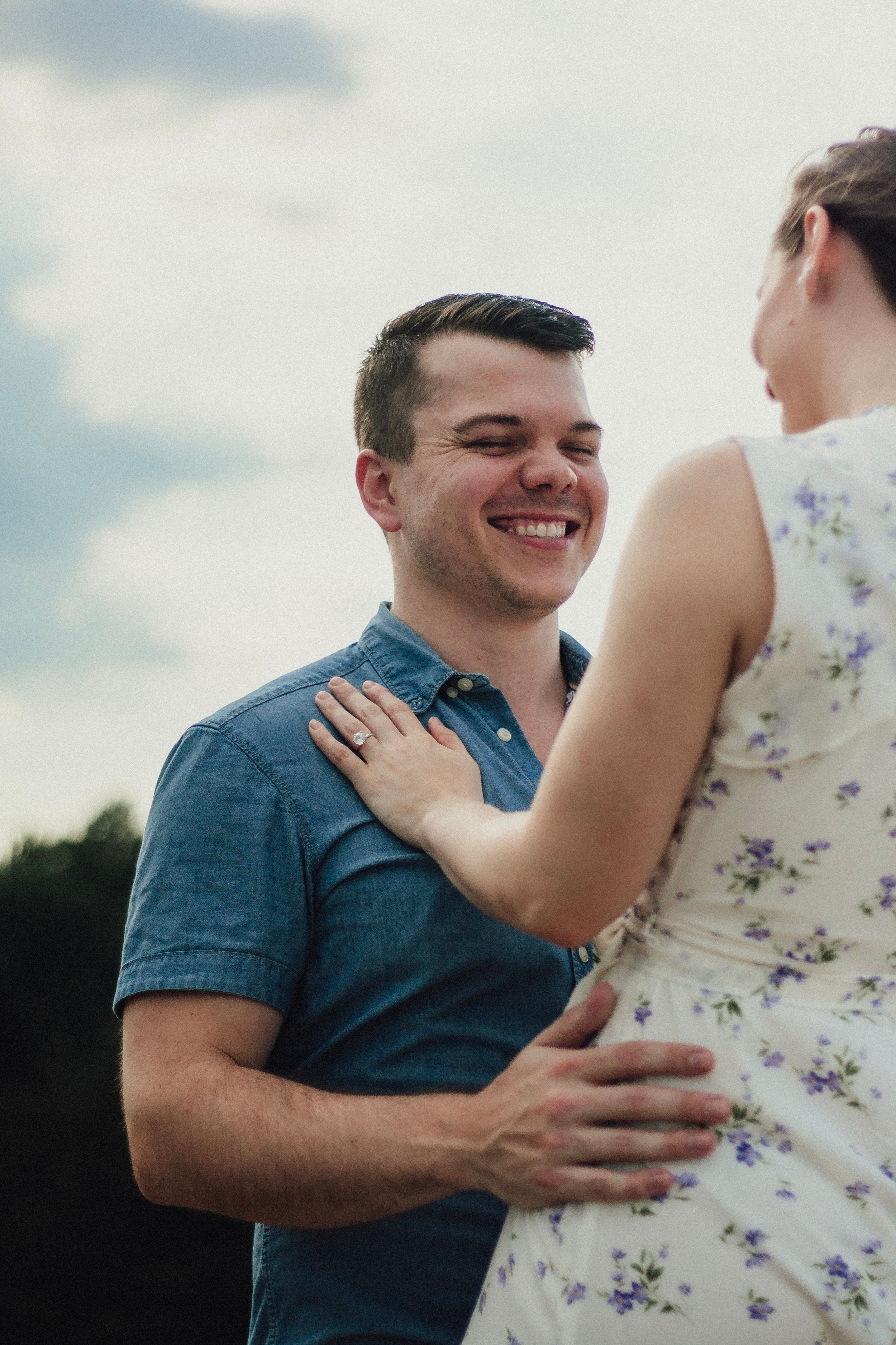 engaged couple smiling at each other in wake forest