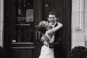 Bride and groom laugh hysterically in front of Teatro Restaurant Calgary