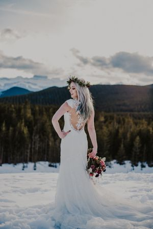 Bride stands in front of mountains at sunset