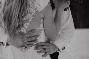 Black and white photo of groom holding bride showing her back of dress