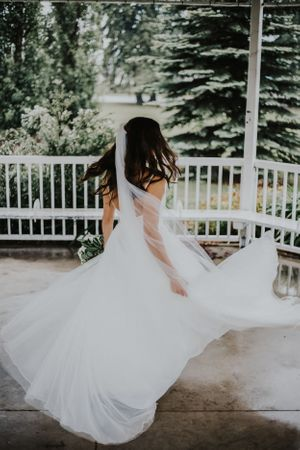 Bride twirls dress in garden gazebo in Olds alberta