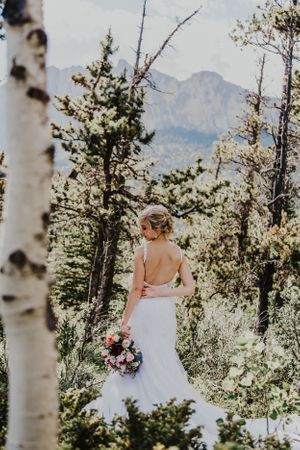 Bride shows off her backless wedding dress in the forest