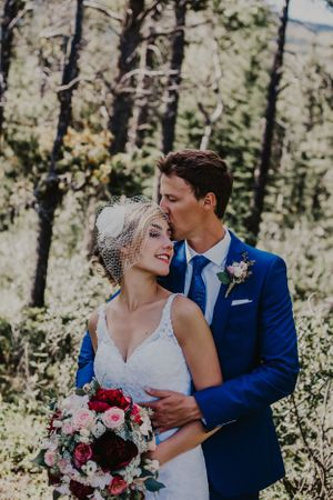 Groom kisses bride's forehead in trees