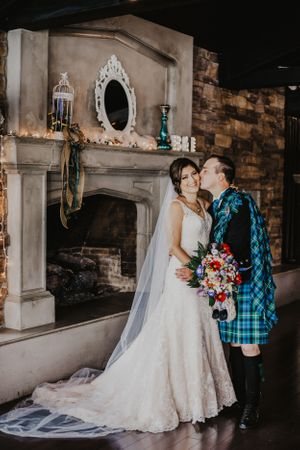 Scottish groom kisses bride in front of fireplace at the Lakehouse YYC
