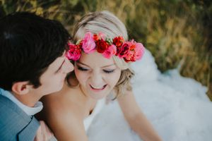 Bride wearing flower crown laughs while groom whispers to her