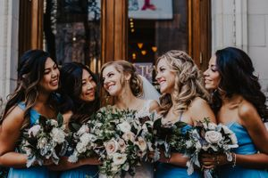 Bride and bridesmaids smile in front of teatro restaurant