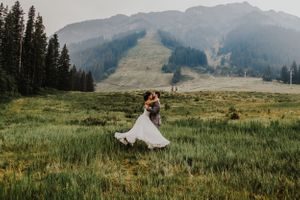 Groom twirls bride around in her dress in front of Mount Norquay