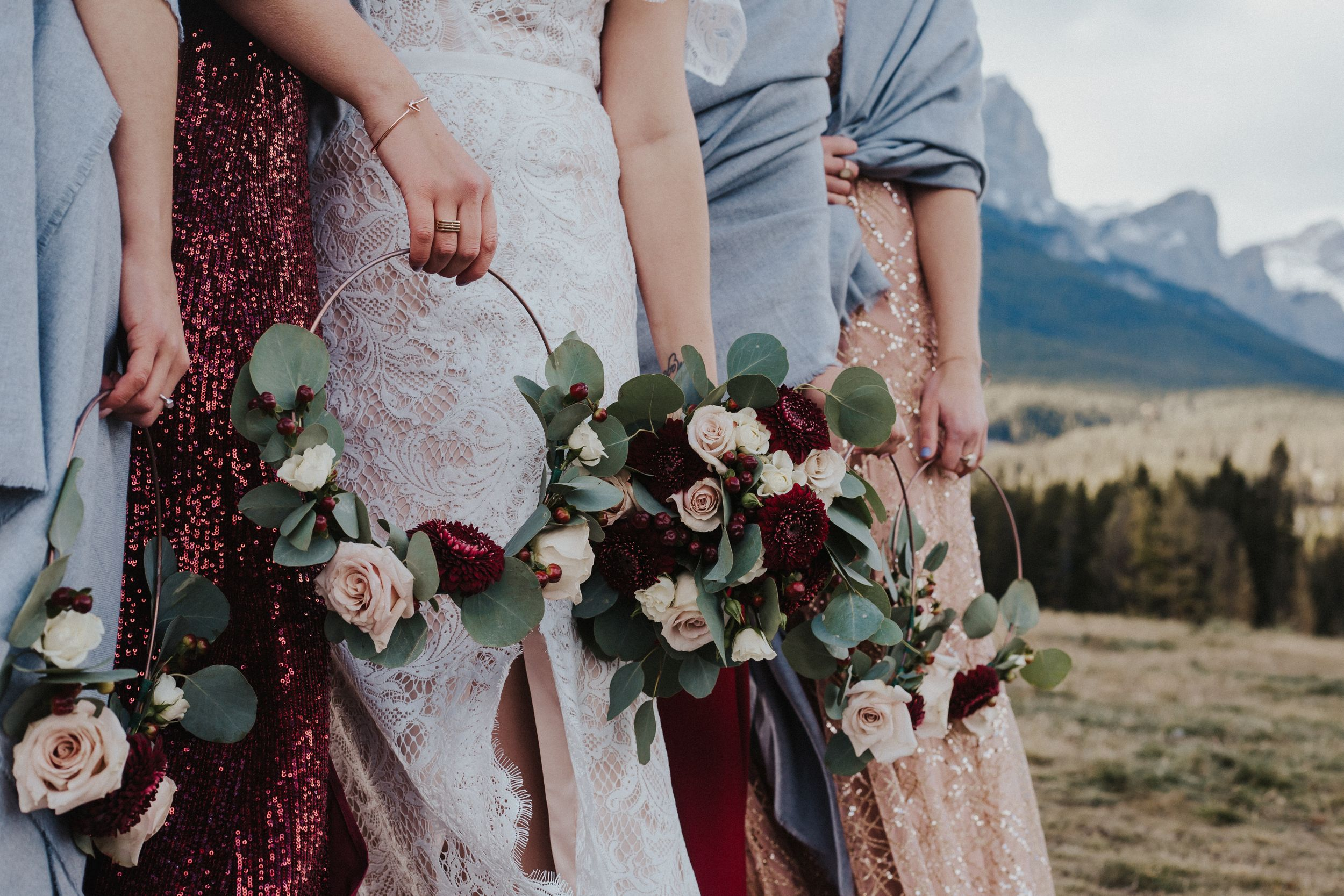 Bride and bridesmaids hold flower rings in front of Canmore mountains