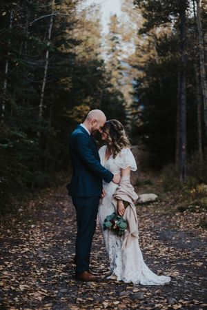 Bride and groom stand forehead to forehead in forest