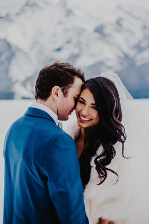 Groom whispers in bride's ear in Banff