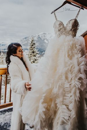 Bride smiles while looking at wedding gown in front of banff mountains