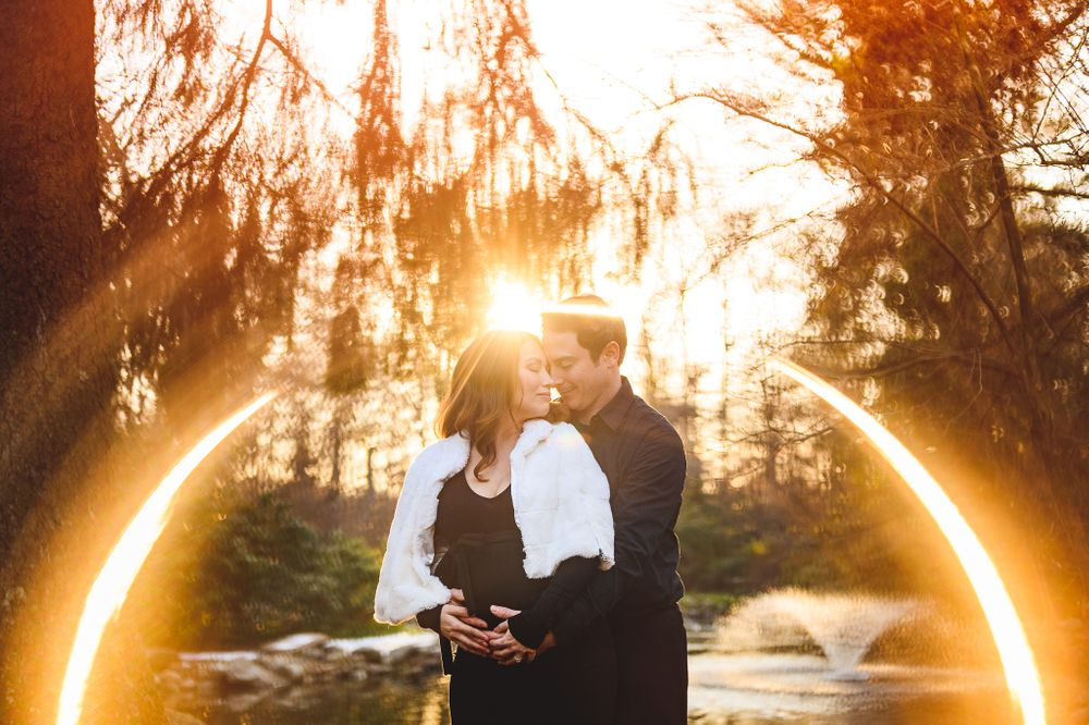 husband hugging pregnant wife in sun flare at sayen gardens