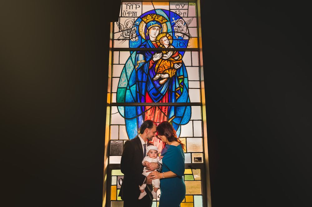 mother and father touching foreheads with baby at christening in front of a church stained glass window