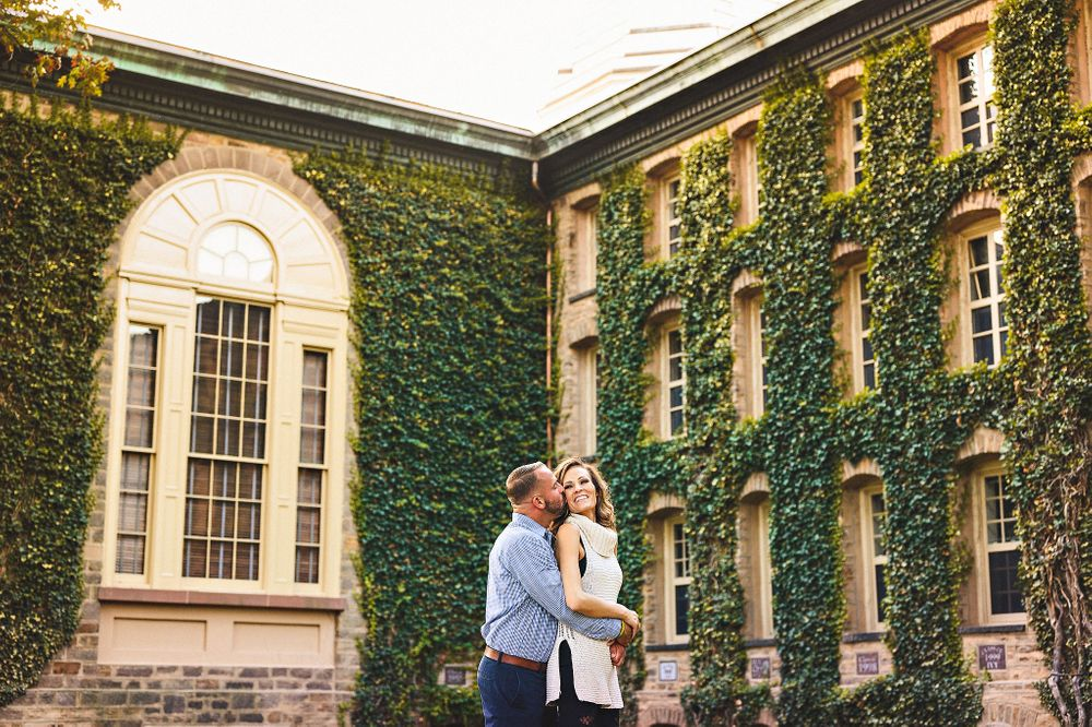 Couple holding each other in front in Princeton in front of green leafed building