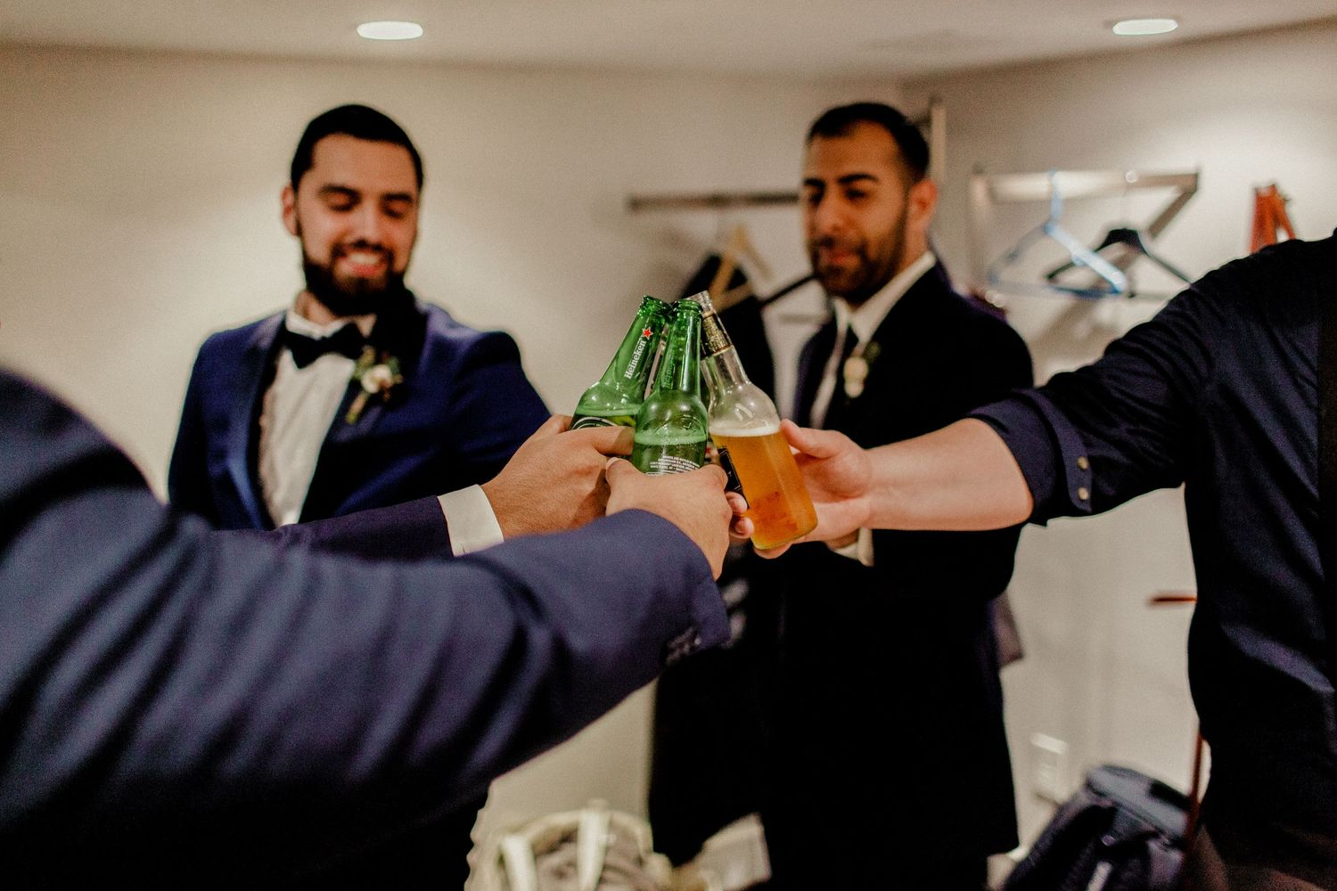 groomsmen cheering beers before wedding ceremony