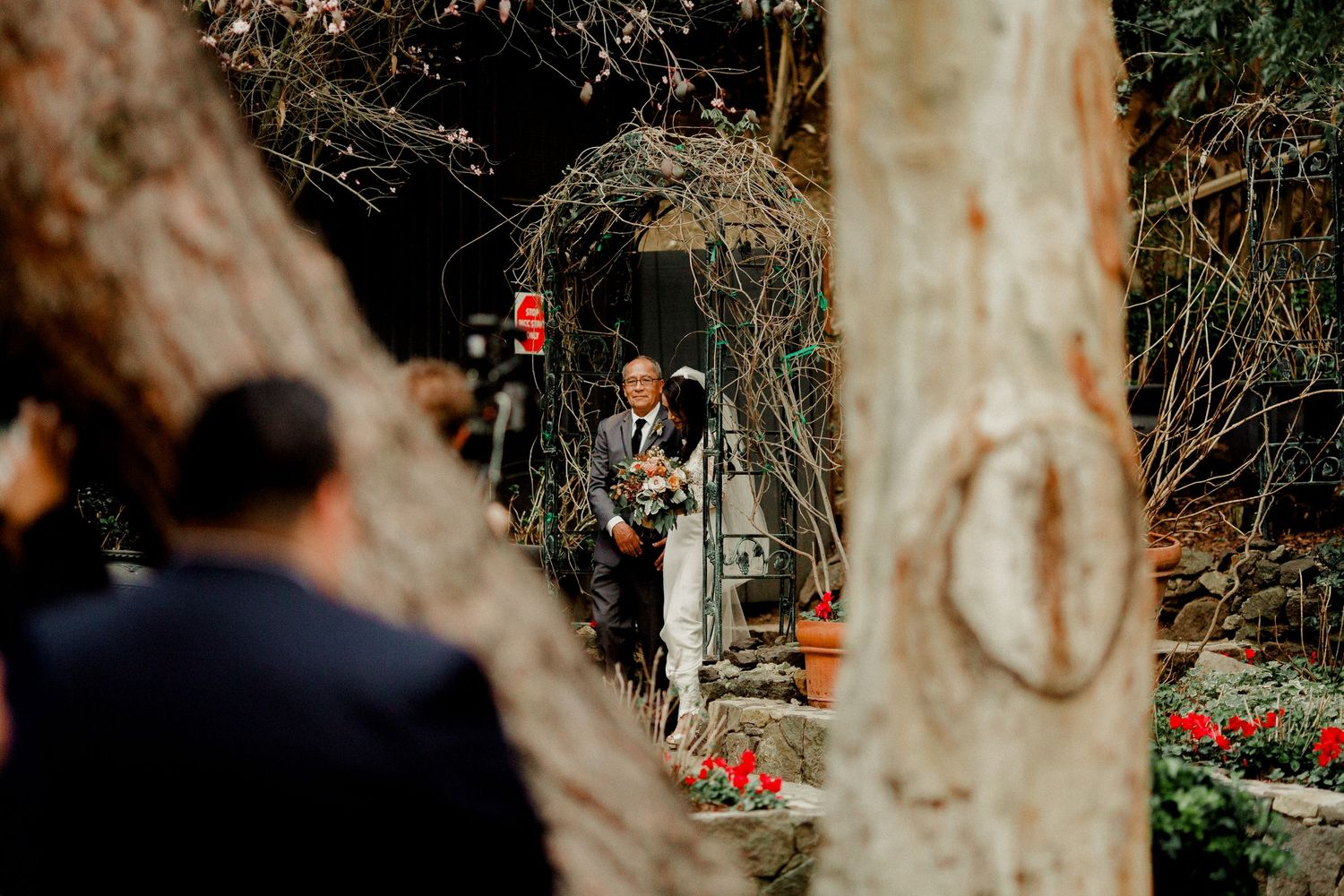 bride seen through trees walking down with father to wedding ceremony