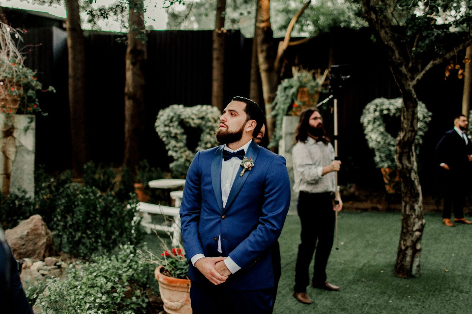 groom holding back tears while preparing for bride to walk down aisle