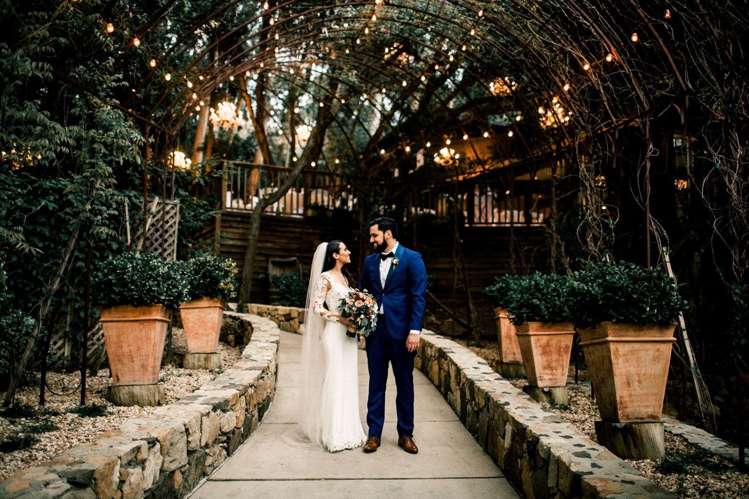 bride and groom standing in front of arch at calamigos ranch birchwood room malibu