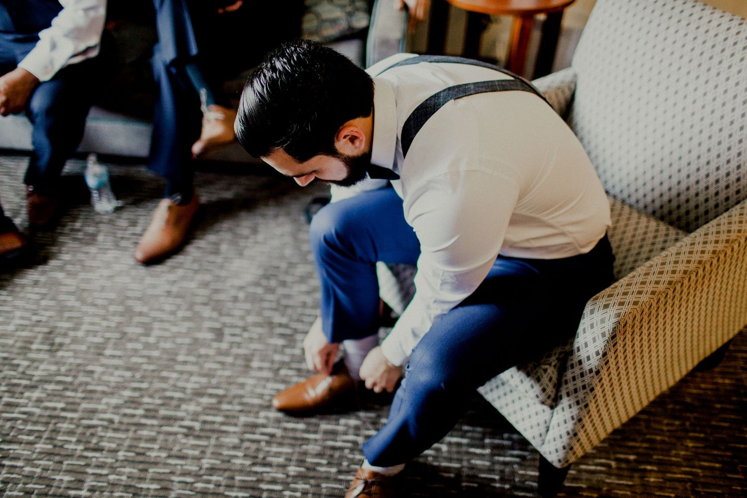 groom putting on dress shoes