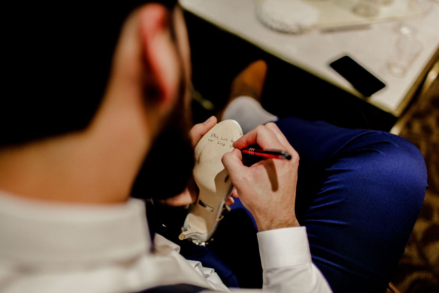 groom writing message on shoe for bride