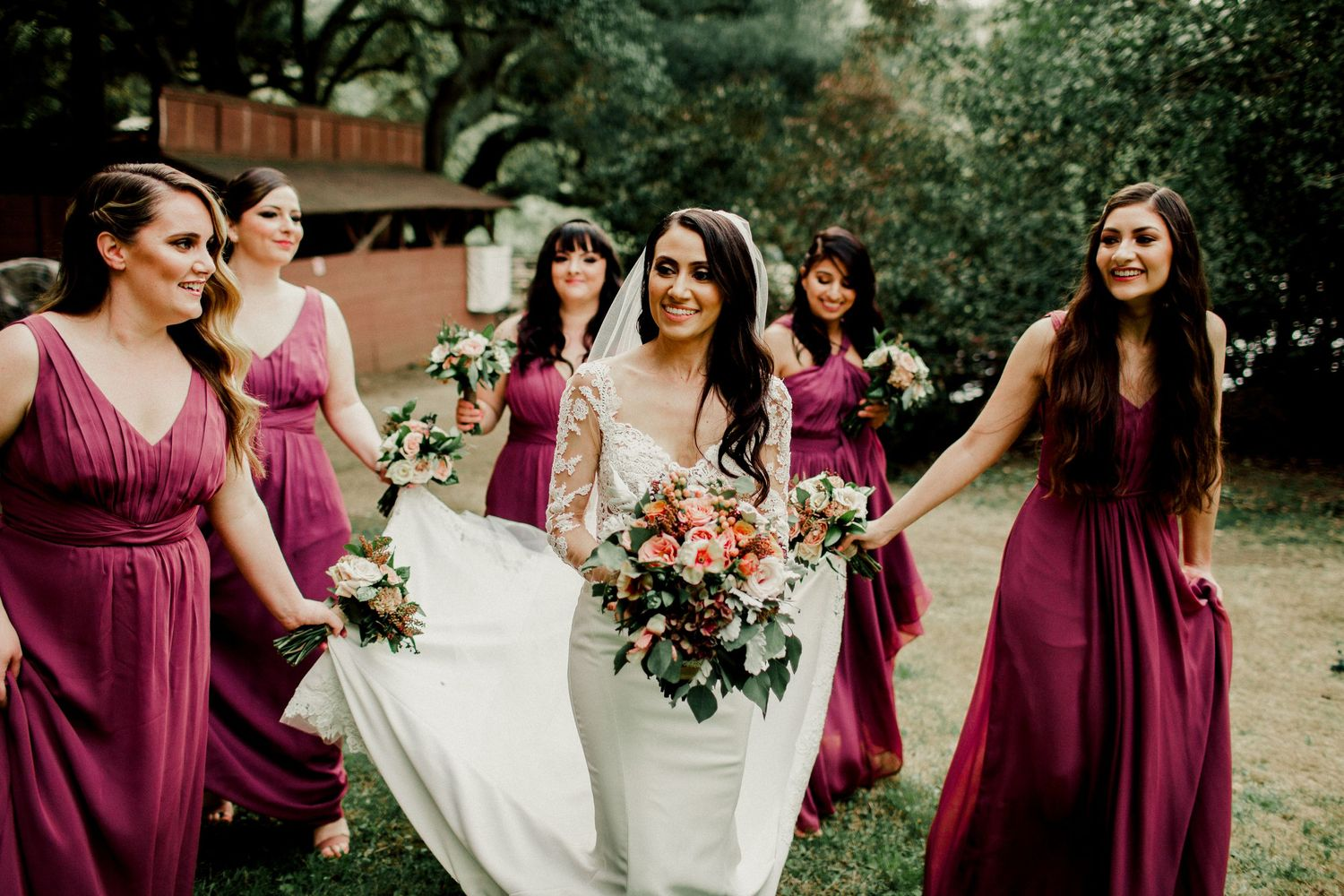 bridesmaids walking with bride helping with dress