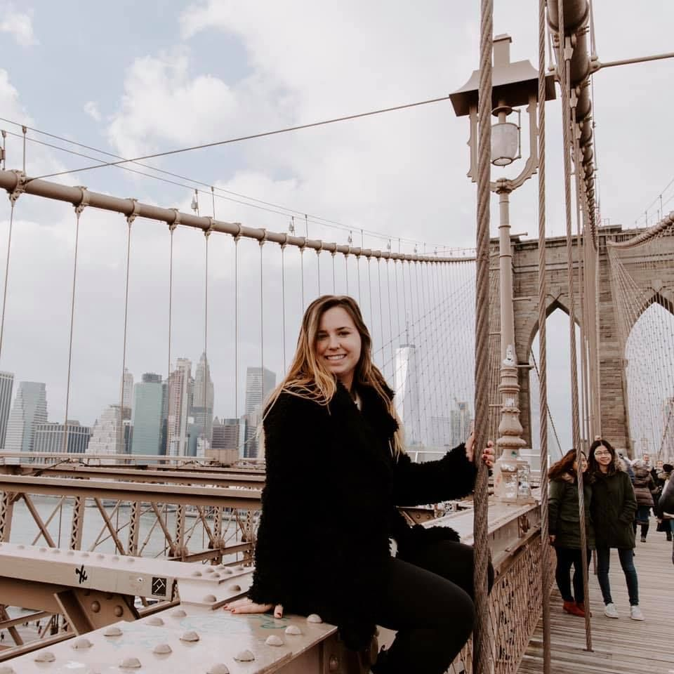 girl sitting on the Brooklyn Bridge with the New York skyline