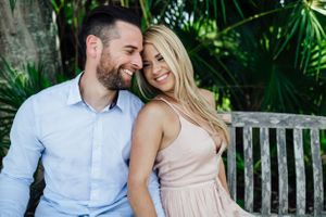 couple smiling at each other while she leans on his chest during an engagement session at Tropical Fairchild and gardens