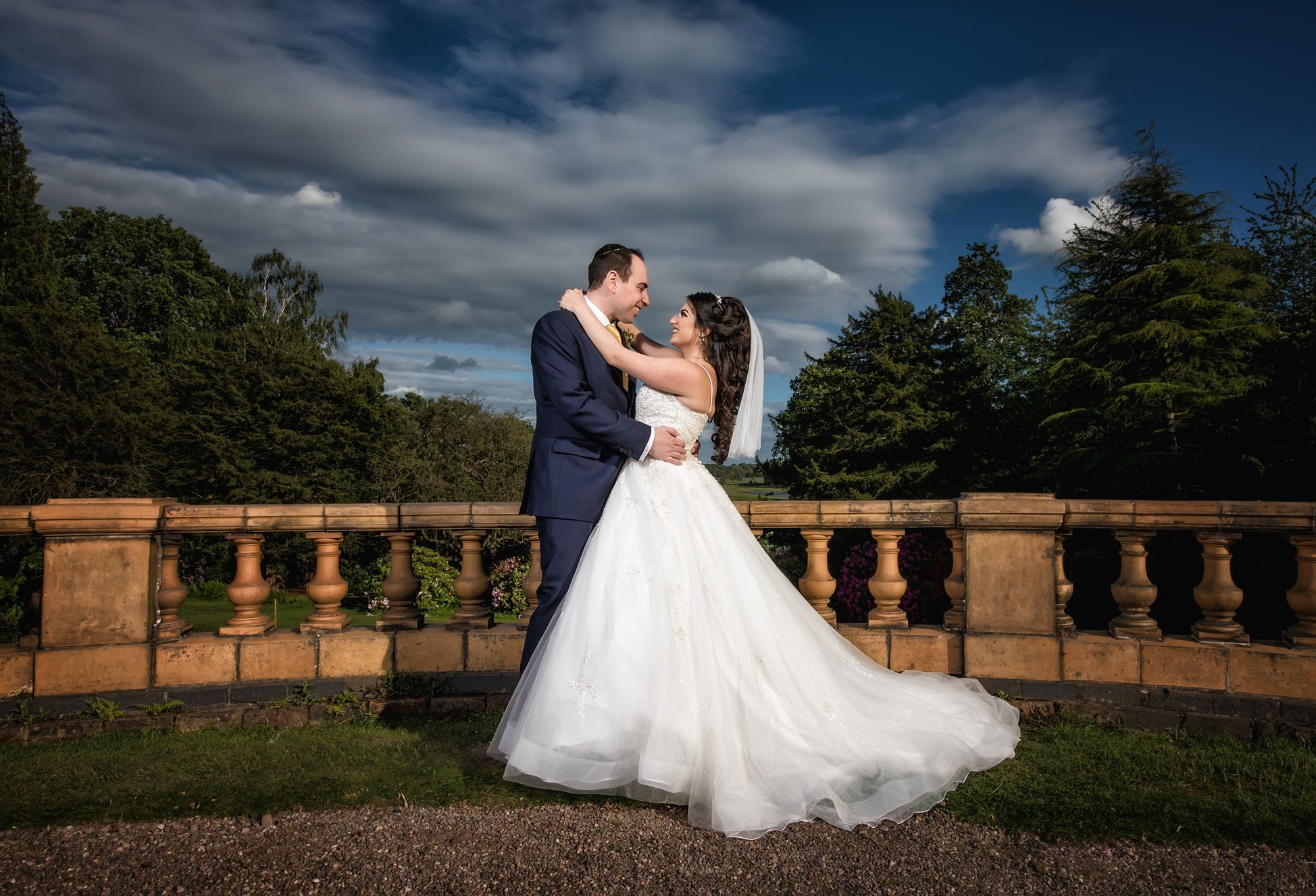 Groom in a smart suit and his bride in white wedding dress embrace each other in the gardens at Tatton Hall