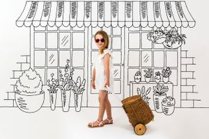 Imaginative and creative photo of a girl shopping using a hand drawn background of a flower shop.