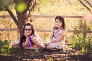 2 sisters soaking up the evening sun in Berwick's Wilson Botanic Park during their family photo session.