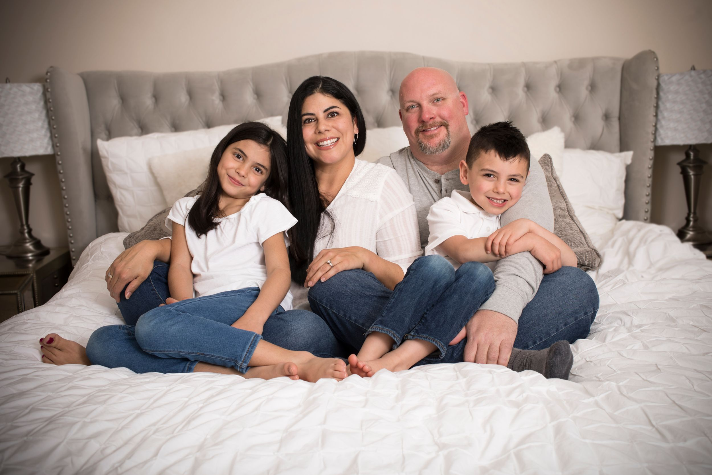 A happy family sitting on a big bed.