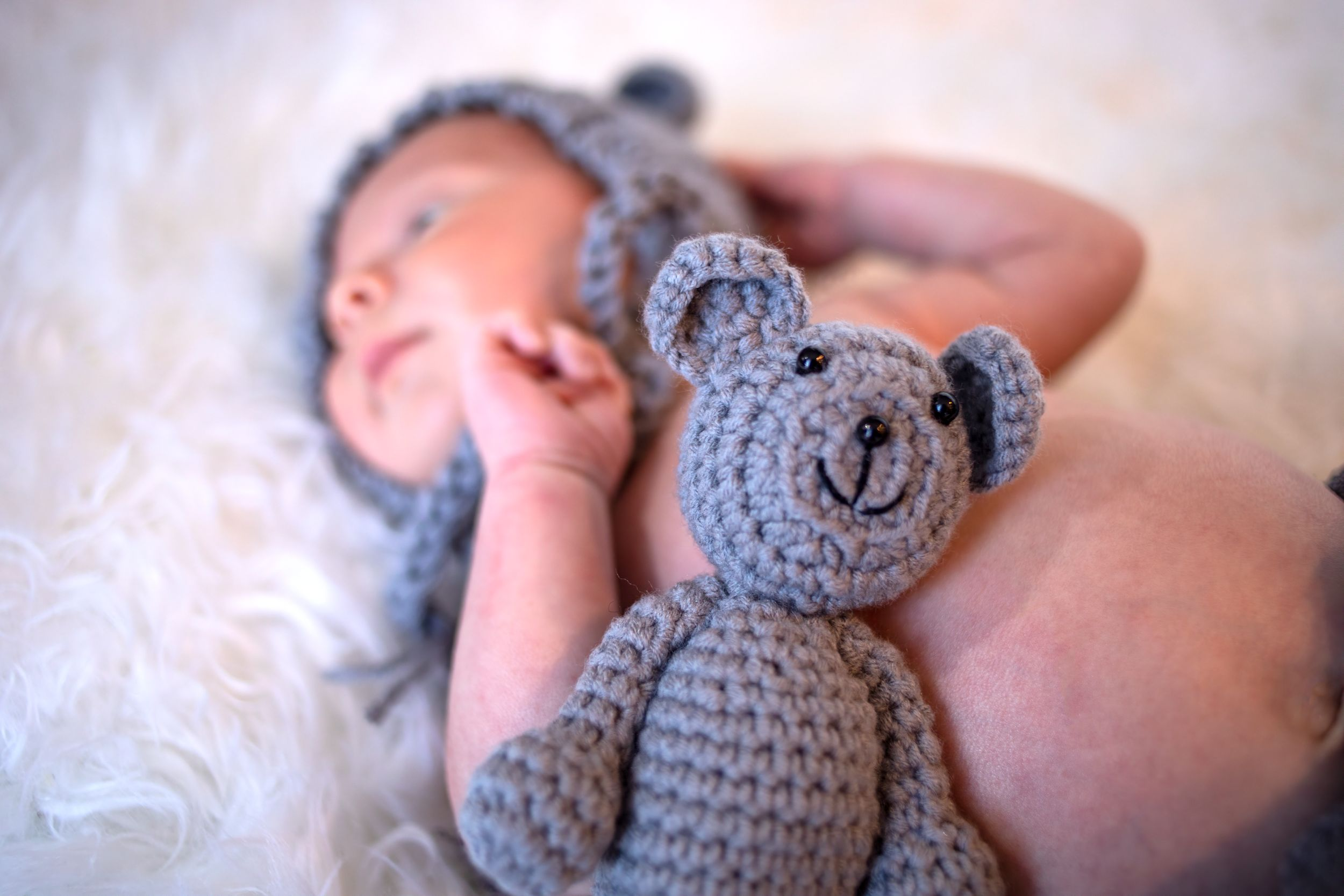 Close up of newborn with a tiny stuffed bear.