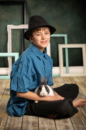 A boy in his hat holding a bunny.