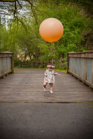 A toddler girl with a giant peach balloon.