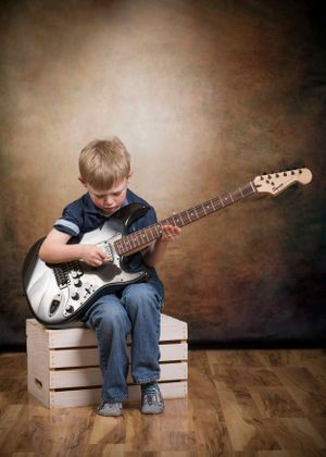 Little boy playing the guitar.