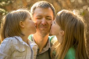 Two little sisters giving dad a kiss on the check at the same time.