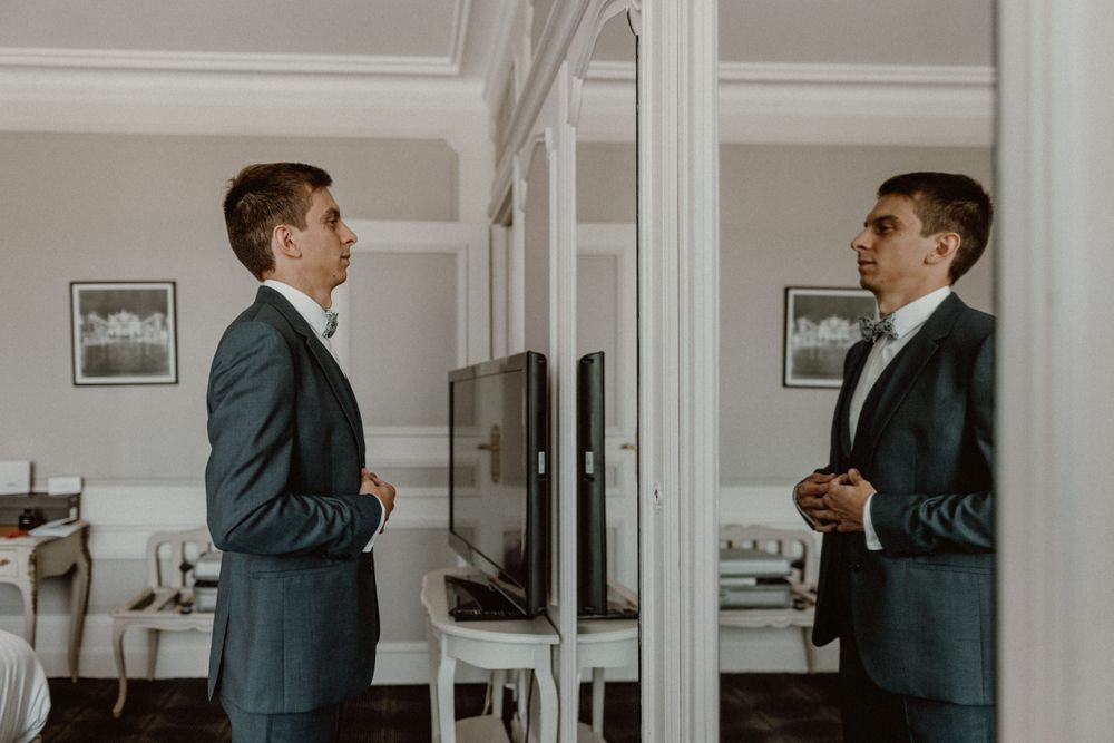 groom facing the mirror in his suit before wedding at l'hotel de la reine Nancy