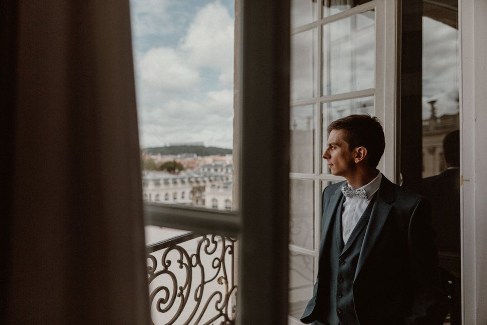 groom looking at the place stanislas before his wedding at Nancy hotel de la reine
