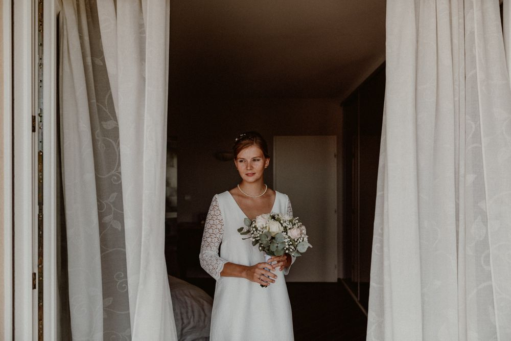 bride getting ready in front of a window with curtains